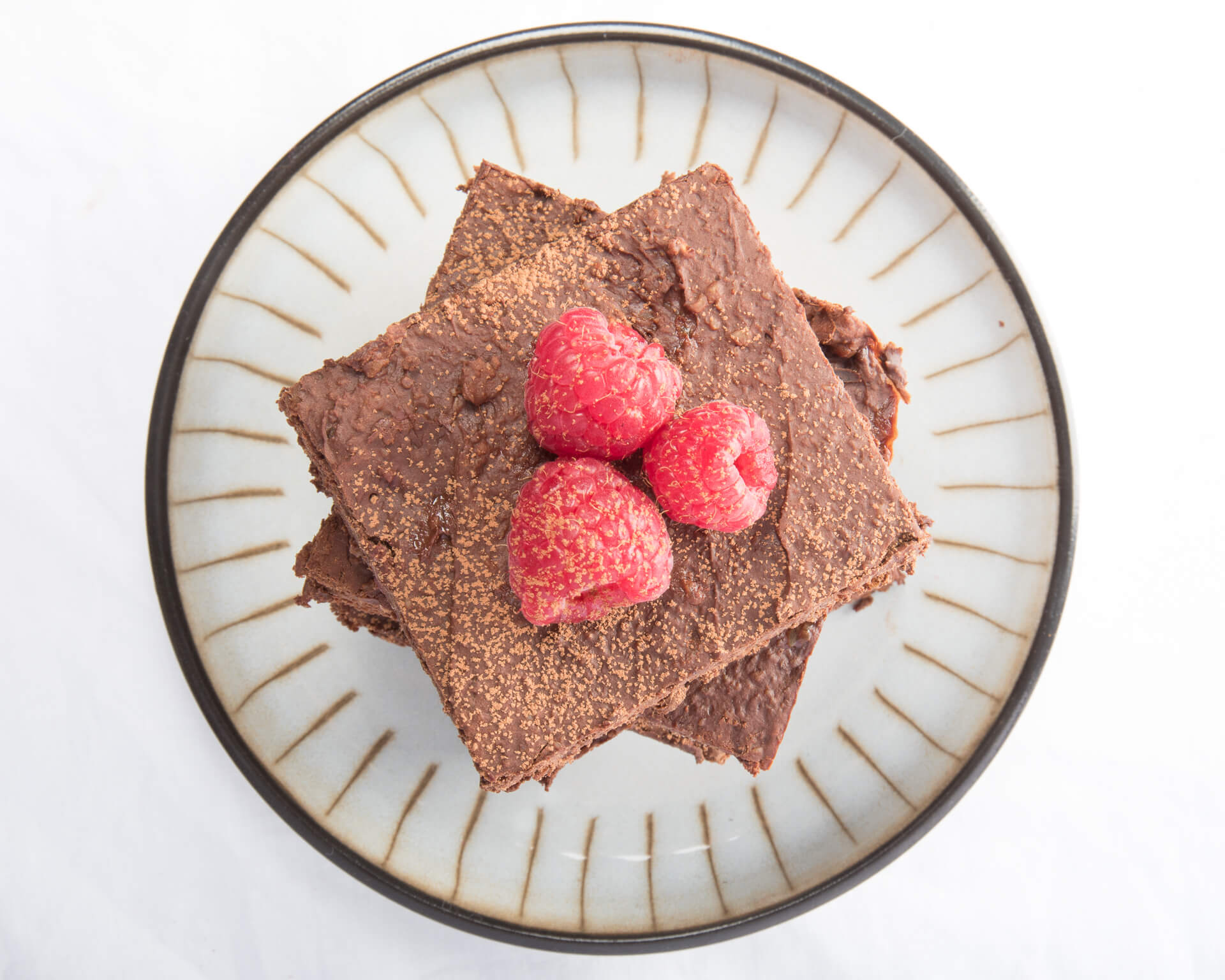 A Stack of Chocolate Brownies Topped With Three Fresh Raspberries Viewed From Above