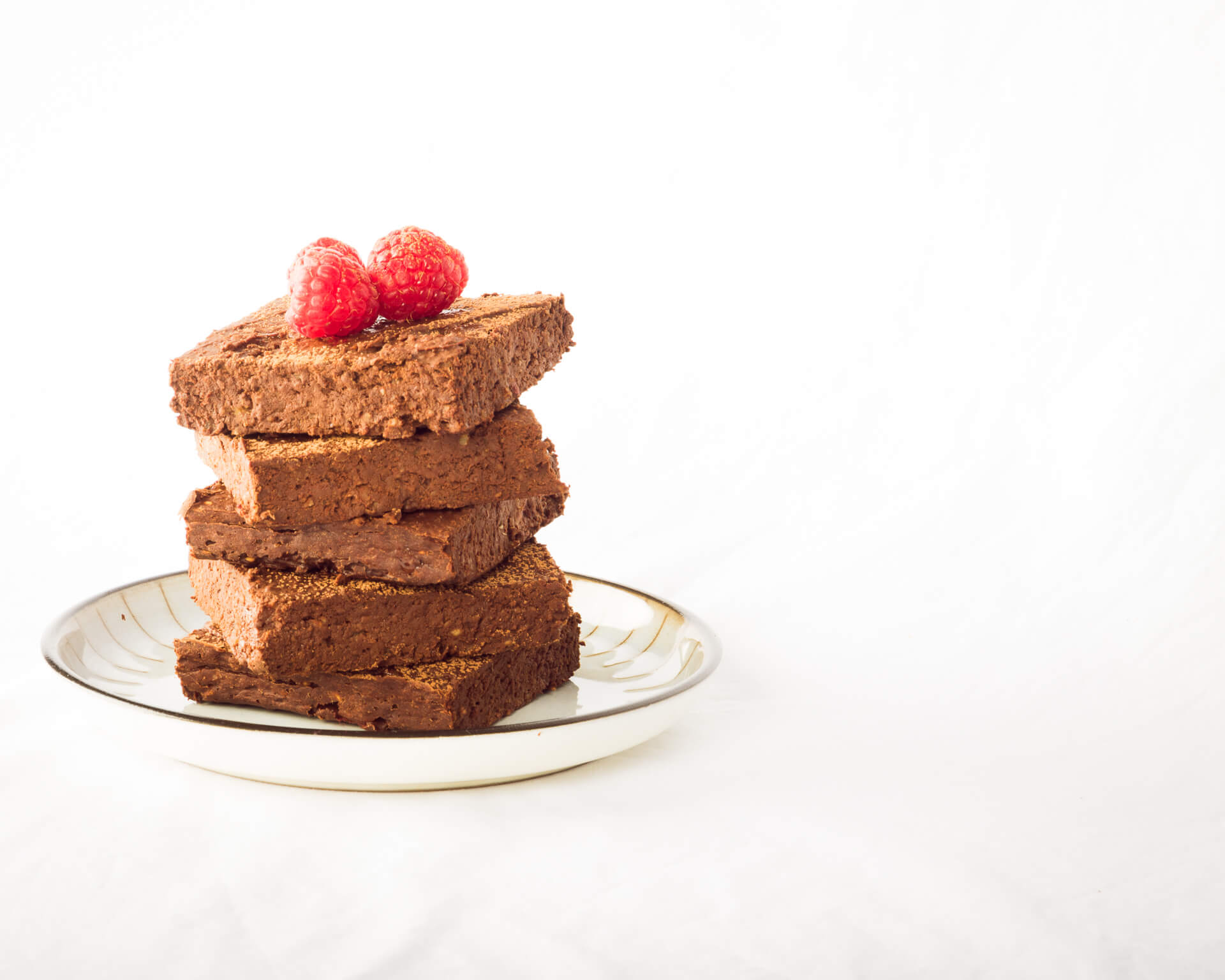 Chocolate Brownies Topped With Three Fresh Raspberries In A Stack On A Plate