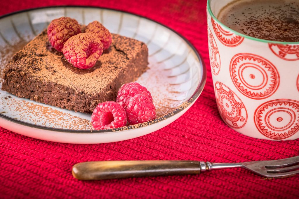 A Chocolate Brownie with Fresh Raspberry Topping Sprinkled With Chocolate On A Plate With A Cup Of Hot Chocolate Next To It