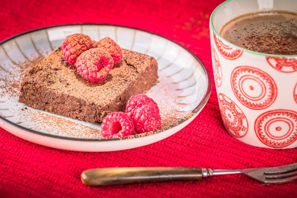 A Gluten Free Chocolate Brownie Topped With Three Fresh Raspberries Sprinkled With Chocolate Dust And A Mug of Hot Chocolate