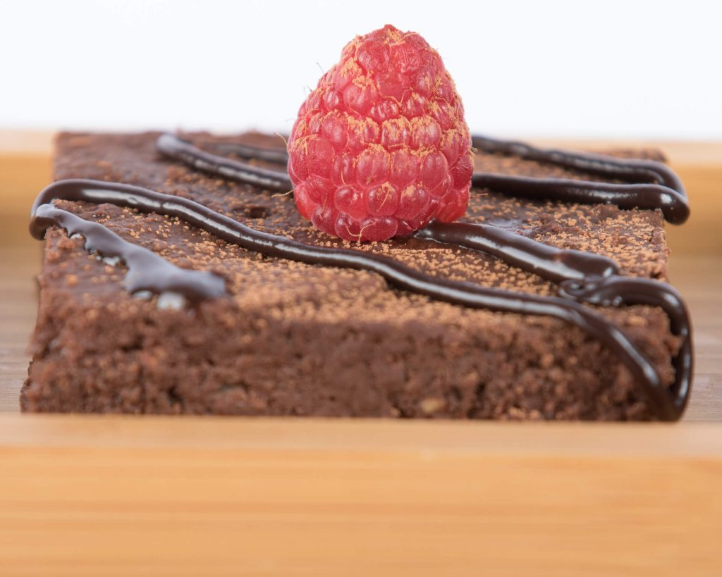 A Gluten Free Chocolate Brownie Topped With A Fresh Raspberry, Chocolate Powder, And Chocolate Drizzle Sauce