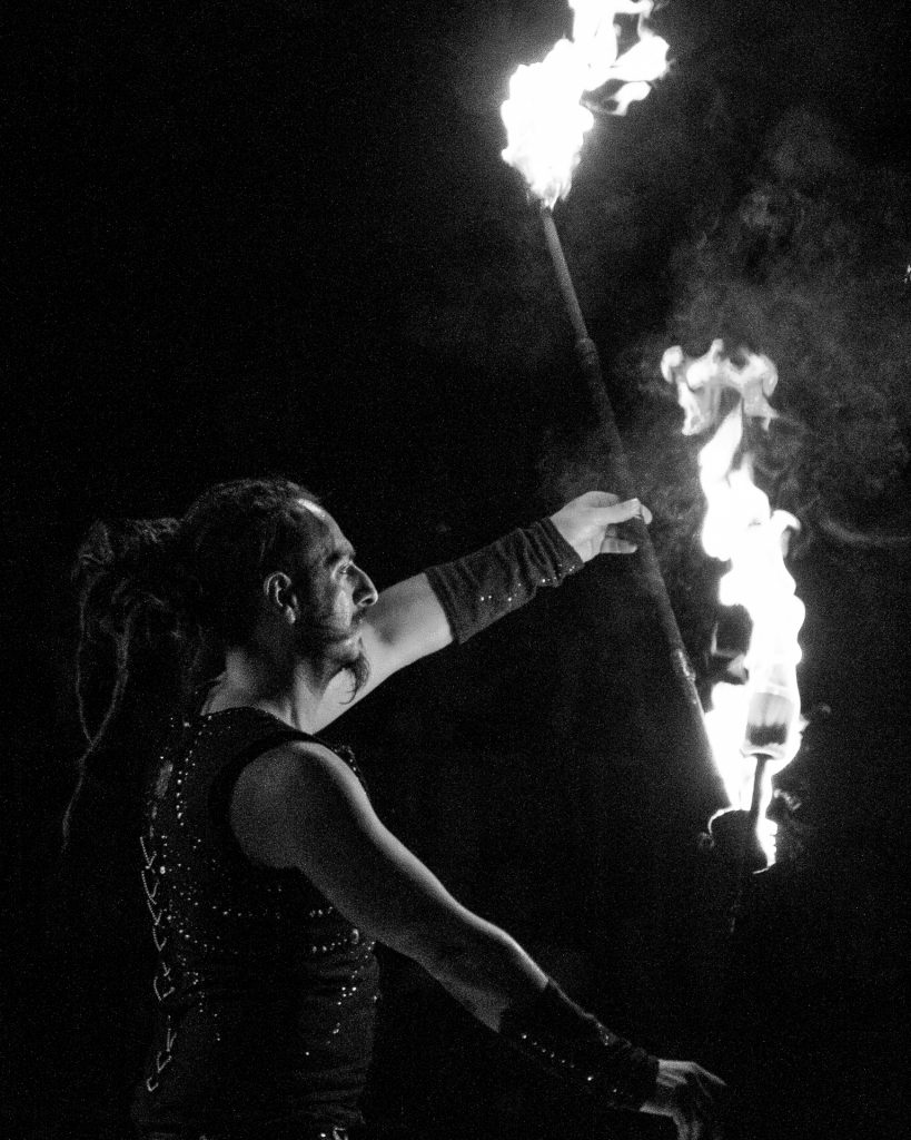 A waist up black & white image of a male fire eater preparing and lighting props for his act just prior to going on stage at a small village festival in Blanzay, France.