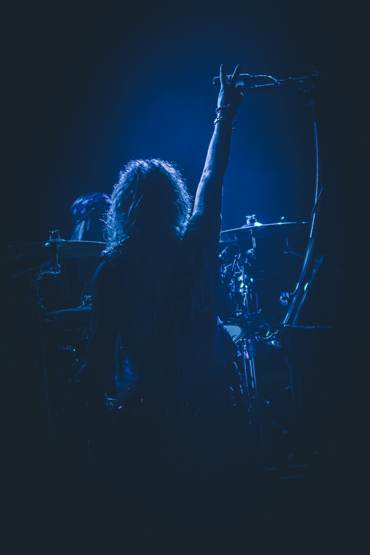 A blue tinted shot of Michael Starr (lead singer of Steel Panther) back to the camera, fingers raised in a Victory Salute facing Stix Zadinia (the Steel Panther drummer) whilst on stage in Birmingham UK in February 2020.
