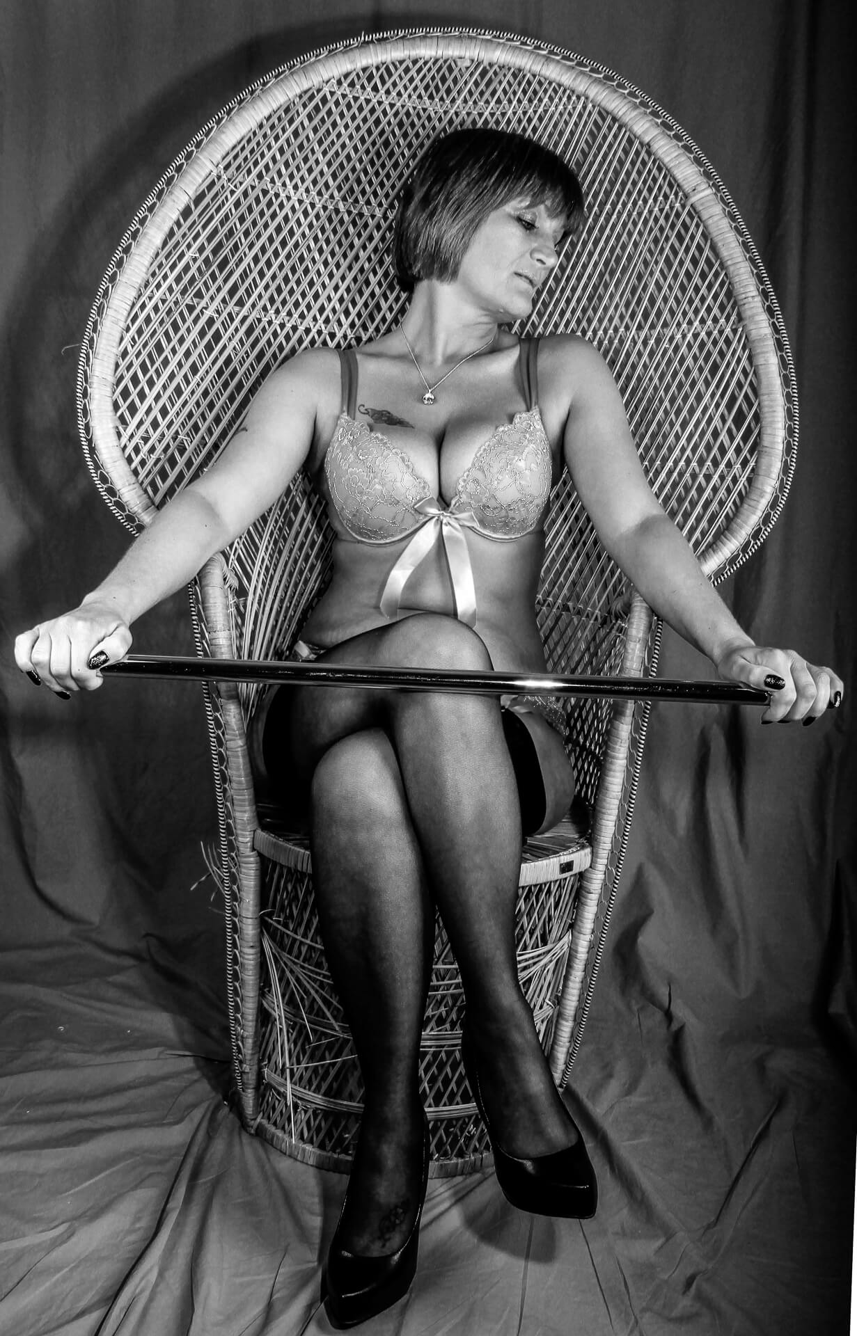 Seen in a full length black & white image whilst sat in a high back bamboo chair is Viv. Viv has her head turned to her left and she is looking slightly down. She has her right leg crossed over her left. Viv wears a lacy bra which enhances her (already fabulous) 'assets', black stockings, and black high heeled shoes. Viv has a cane grasped between her hands which are held out at her knee height.
