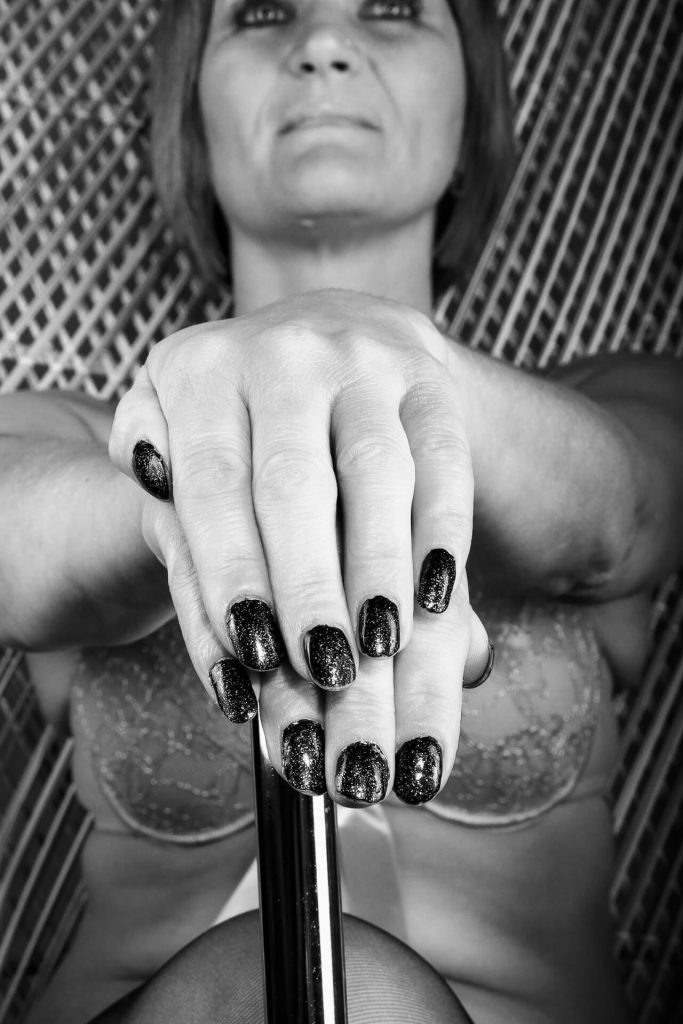 Seen in a close up black & white image whilst sat in a high back bamboo chair is Viv. Or to be more accurate Viv's hands. She holds them, fingers outstretched and painted nails on show, on top of a black silver top cane which reaches just above her knees as she crosses her legs.   Viv has her head held up and tilted slightly back, she is looking up and above the camera. Viv wears a lacy bra which enhances her (already fabulous) 'assets', black stockings, and black high heeled shoes (which are out of shot).