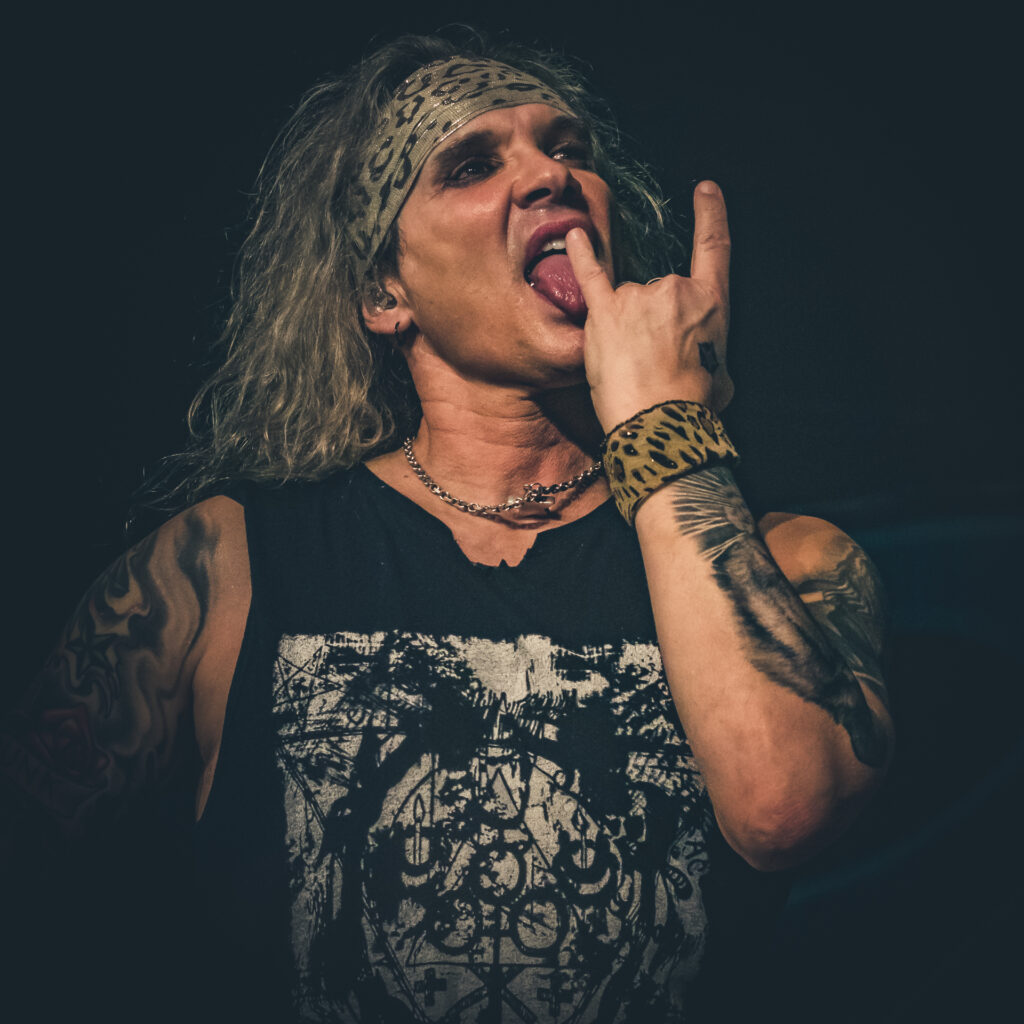 A chest up shot of Michael Starr (lead singer of Steel Panther) as he licks the little finger of his left hand whilst it is formed in a 'Horns Up' salute whilst on stage in Birmingham UK in February 2020.