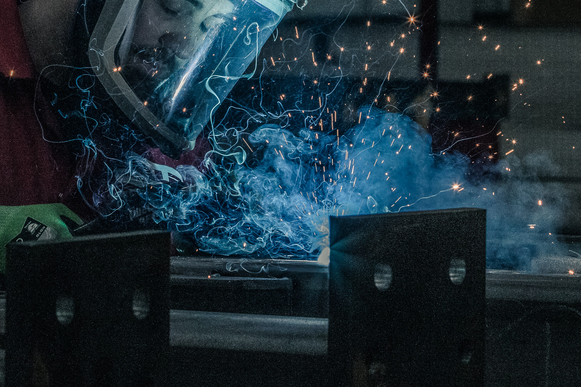 A colour close up image (head & hands) of a welder working on a steel beam. The image has a blue tinge to it from the welding process. There are smoke and sparks present as he works (the sparks are actually incandescent droplets with a temperature of around 1300degrees C!). The welder wears a full face welding helmet and protective clothing.