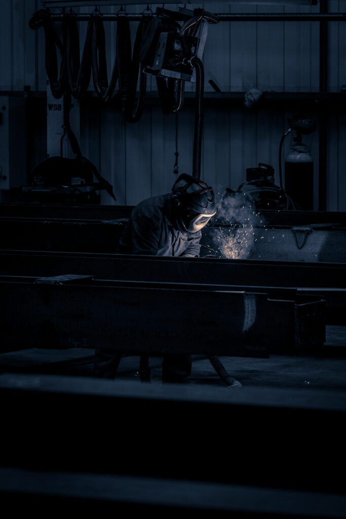 A colour image taken at distance of a welder working on a steel beam. The image has a grey/blue tinge to it. There are sparks present as he works (the sparks are actually incandescent droplets with a temperature of around 1300degrees C!). The welder wears a full face welding helmet and protective clothing. The glow from the welding process illuminates his helmet & chest.
