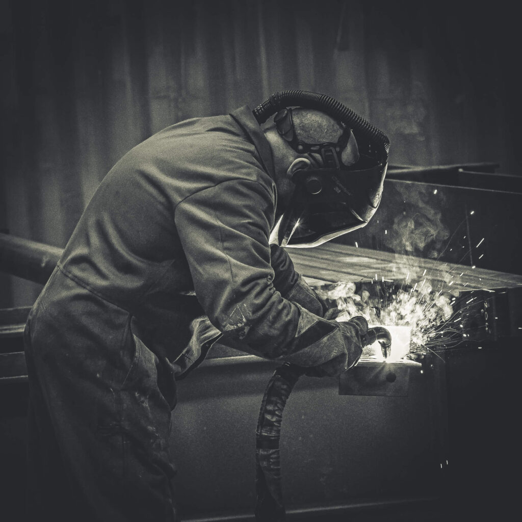 A welder who wears full protective equipment is seen welding in a factory environment.