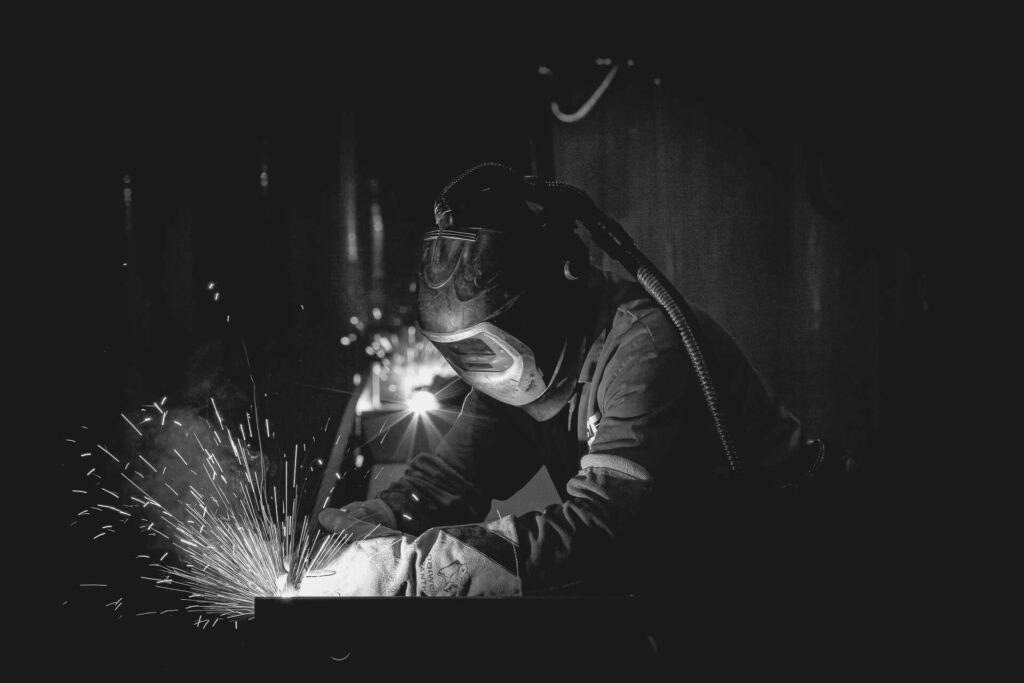 A black & white waist up image of a welder working on a steel beam. The light from the welding process lights up his helmet and hands. There are sparks visible as he works, (the sparks are actually incandescent droplets with a temperature of around 1300degrees C!). The welder wears a full face welding helmet with a built in extraction system, and full protective clothing.