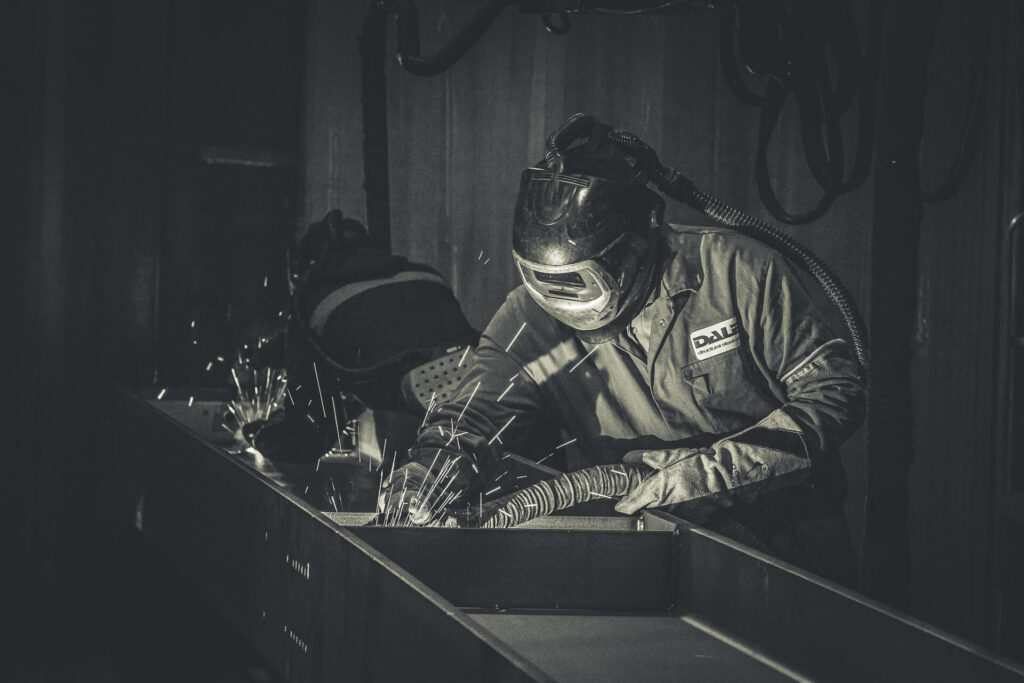 Two welders, in full protective equipment, are seen hard at work. The welder closest to the camera is seen front on whilst welding what appears to be internal support to a beam. The other is facing away, again welding an internal support, his respirator filter pack can be seen on his waist.