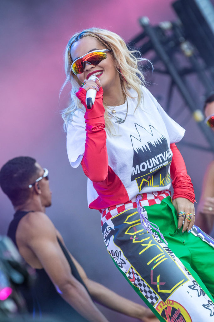 A colour image of a smiling Rita Ora performing on the main stage of the IoW Festival 2018.