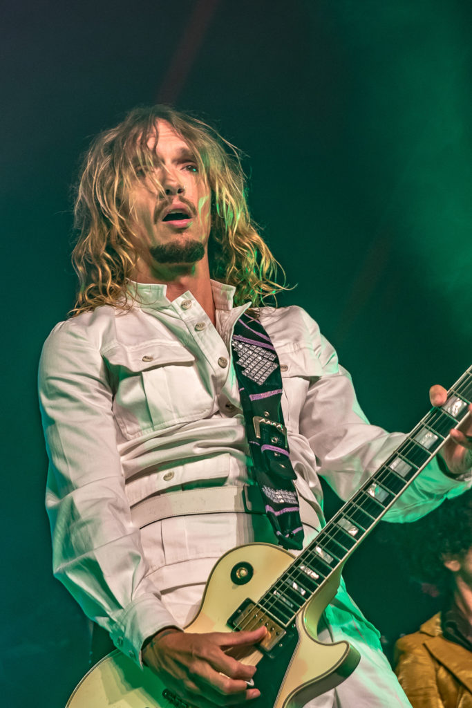 A waist up colour shot Justin Hawkins of The Darkness playing guitar on the Main Stage at Lakefest 2019