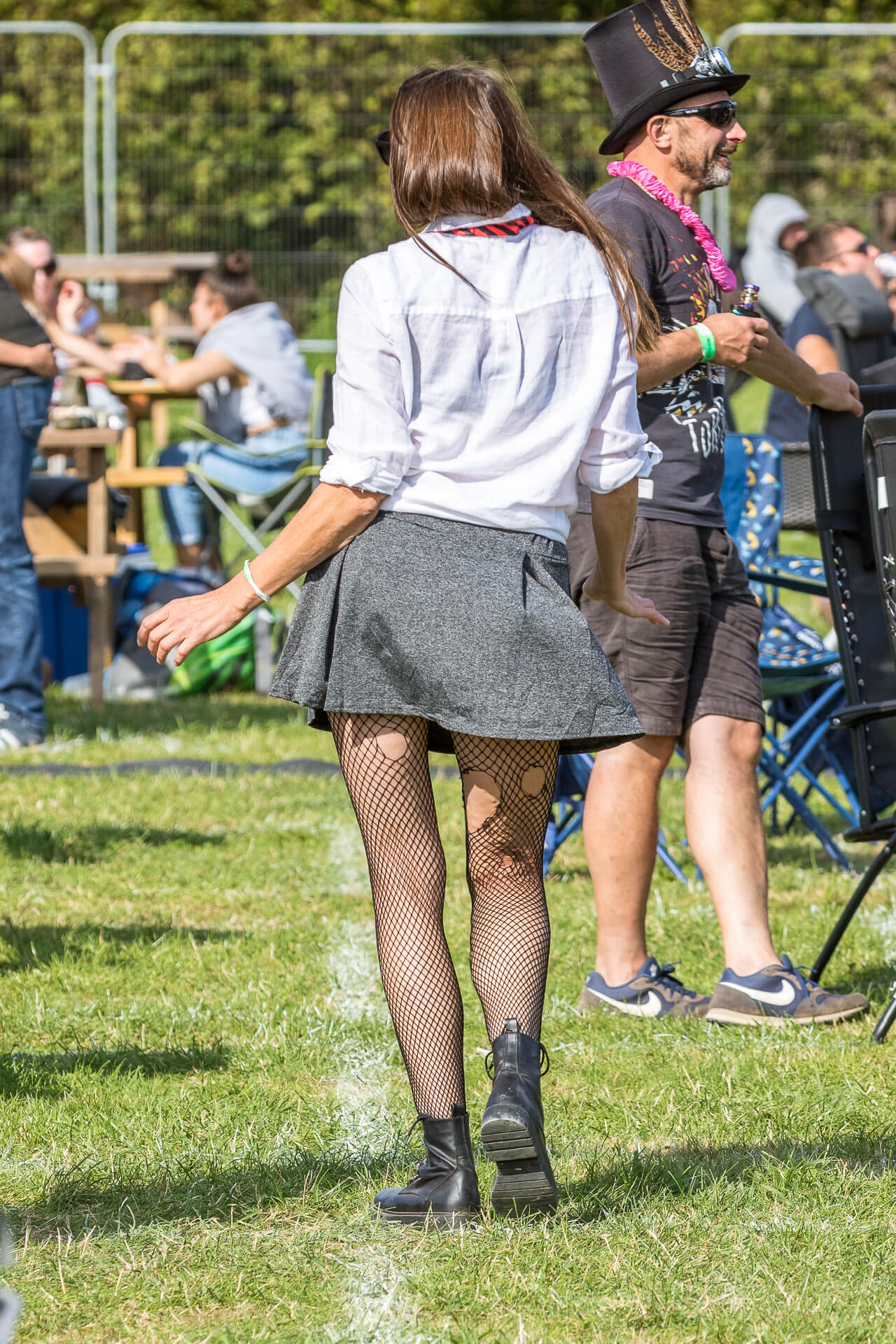 A full length colour image of a long brown haired female festival goer taken at The Bredon Cider Festival 2020 as she dances away from the camera. She wears a white shirt, with rolled up sleeves, a red & black tie, a short grey skirt, and torn fishnet tights, along with black ankle boots.