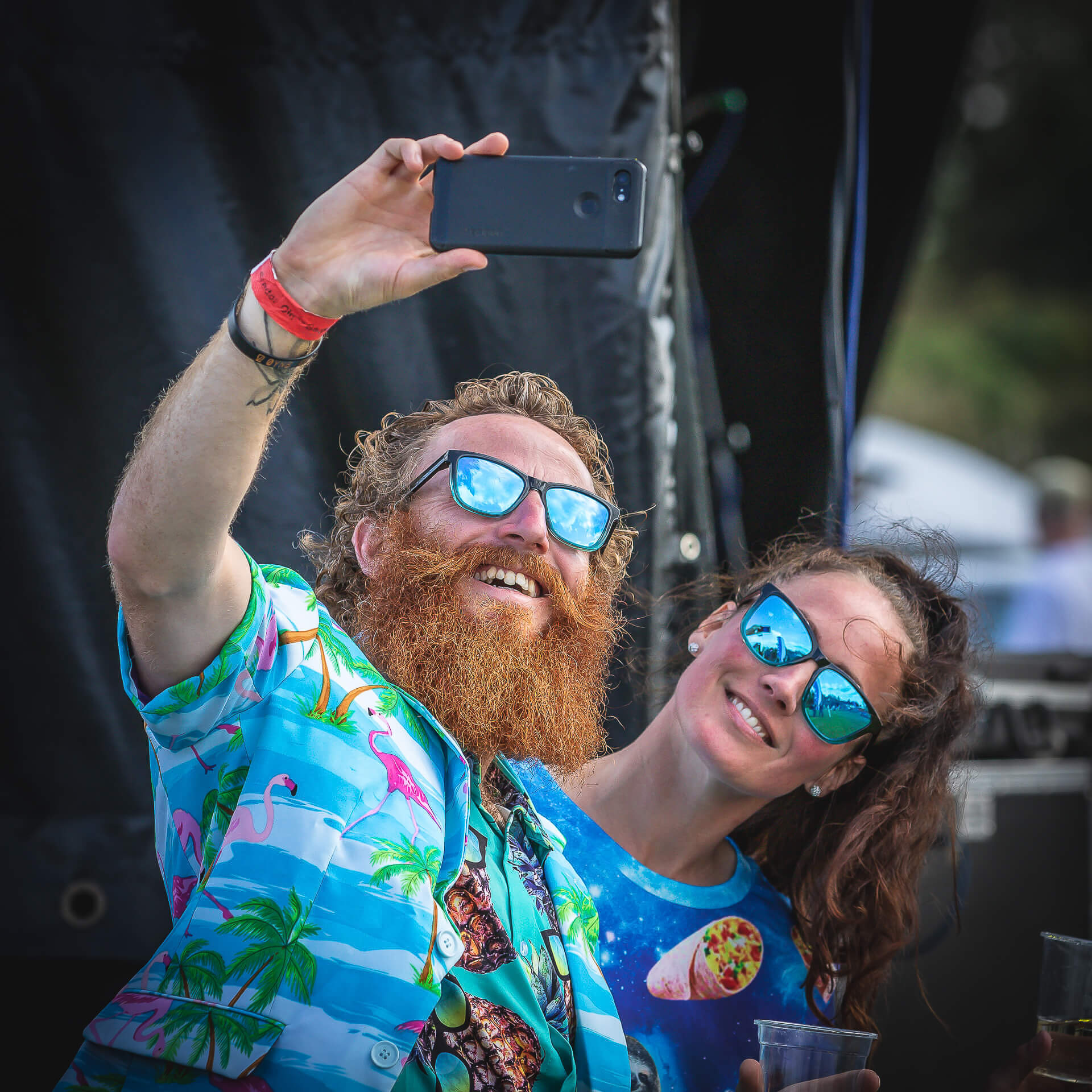 A couple 'smile for the camera' whilst dressed in colourful Hawaiian style dress and vivid blue sunglasses whilst taking a selfie on a mobile phone during the Brendon Cider Festival 2020.