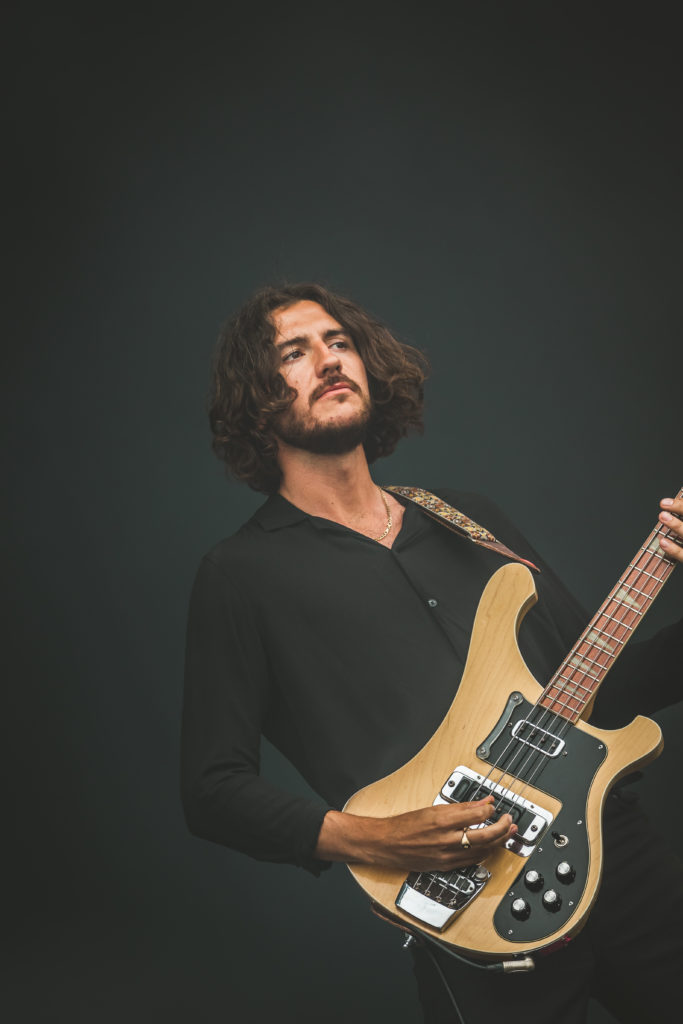 Charlie Salt of Blossoms ( @Chaz_Salt ) Bassist of Blossoms looks into the audience whilst performing on stage at The Isle of Wight Festival 2018.