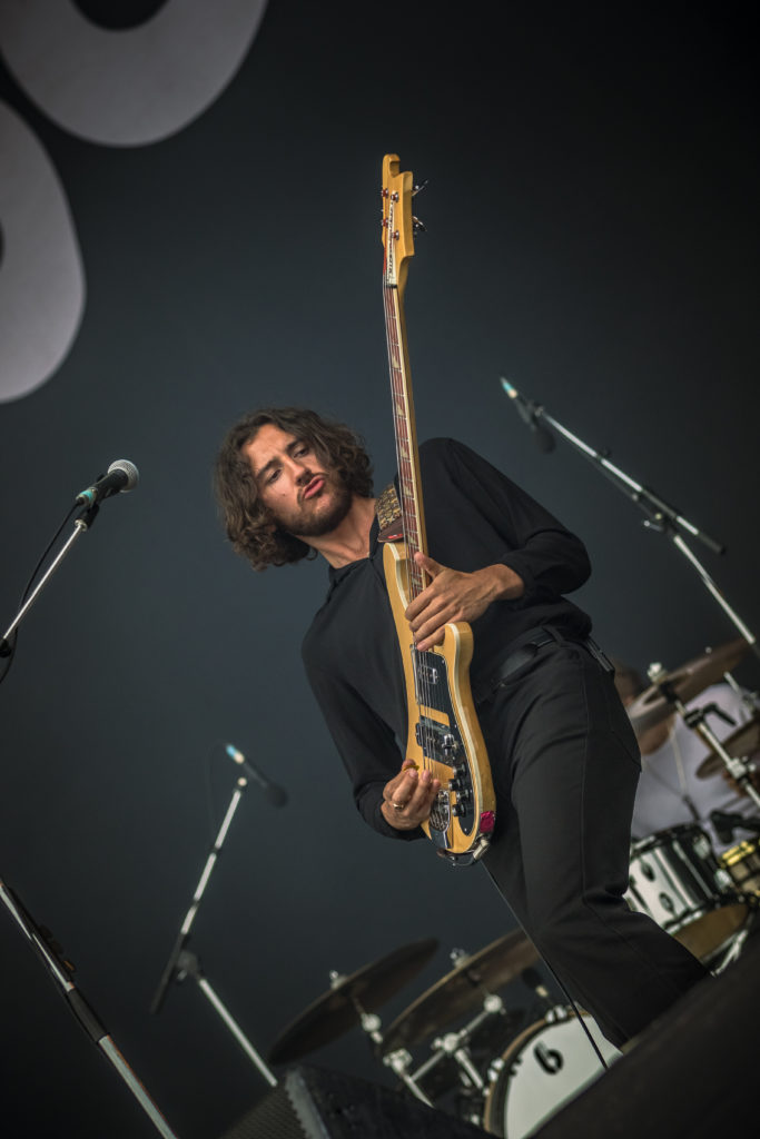 Charlie Salt of Blossoms ( @Chaz_Salt ) Bassist of Blossoms purses his lips whilst performing on stage at The Isle of Wight Festival 2018.