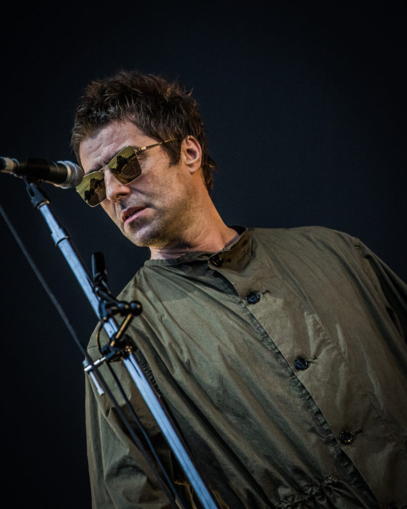 An angled head & shoulders shot of Liam Gallagher approaching the mic on the Main Stage of The Isle of Wight Festival 2018