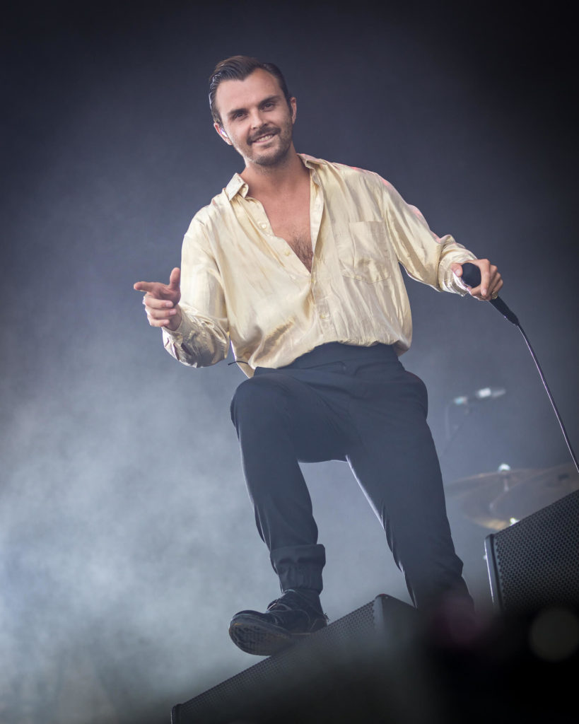 A full length body shot of an open shirted Theo David Hutchcraft, singer with Hurts looking directly at the camera whilst on stage at the Isle of Wight Festival 2018.