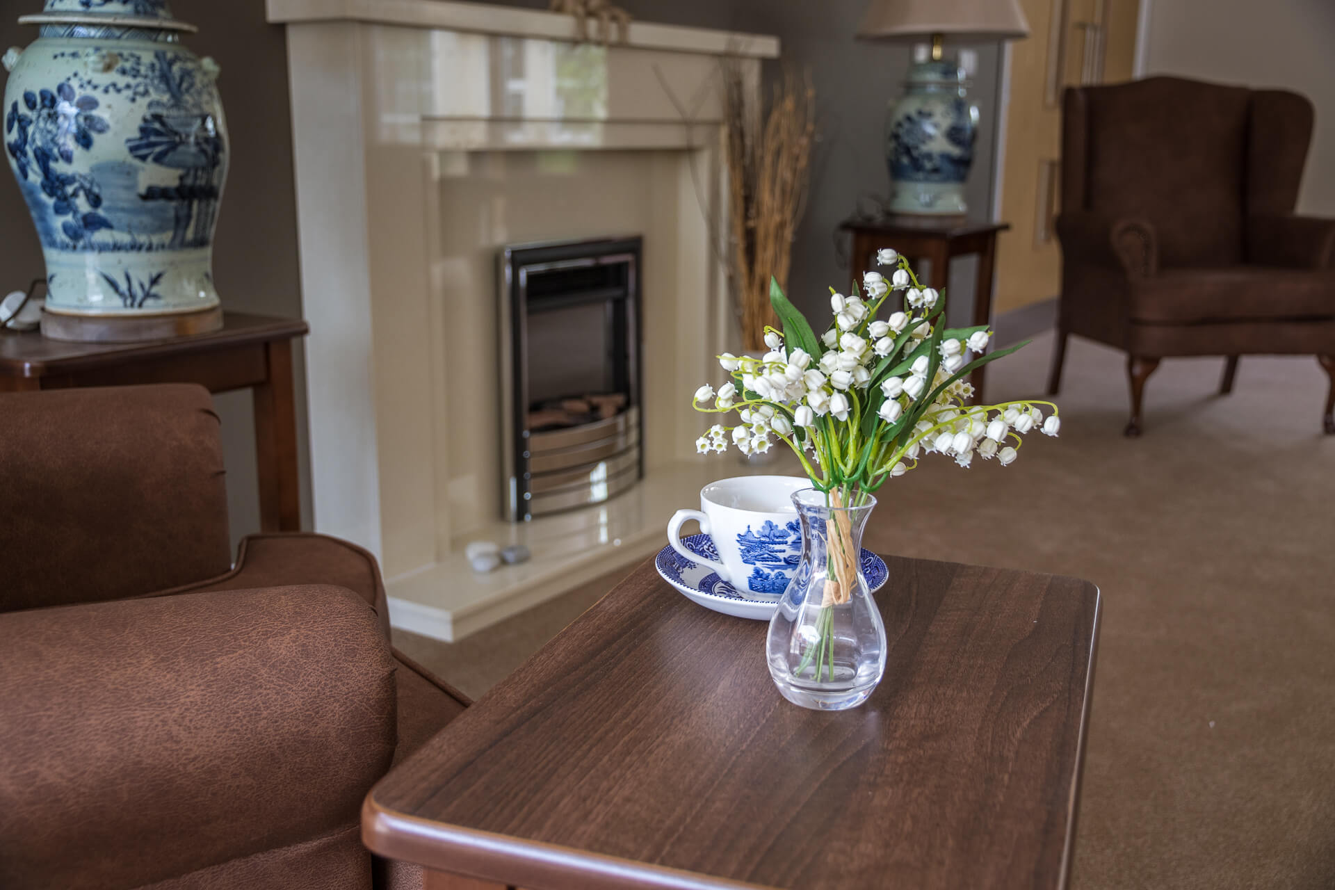A colour image of part of the interior furniture within a community room at The Lawns Care Home, Kempsey, Worcestershire. It shows (in close up) part of an occasional table, with a blue and white cup & saucer, and a small vase with snowdrops upon it.  There is also a gas fire place and sections of two brown coloured high back armchairs within view.