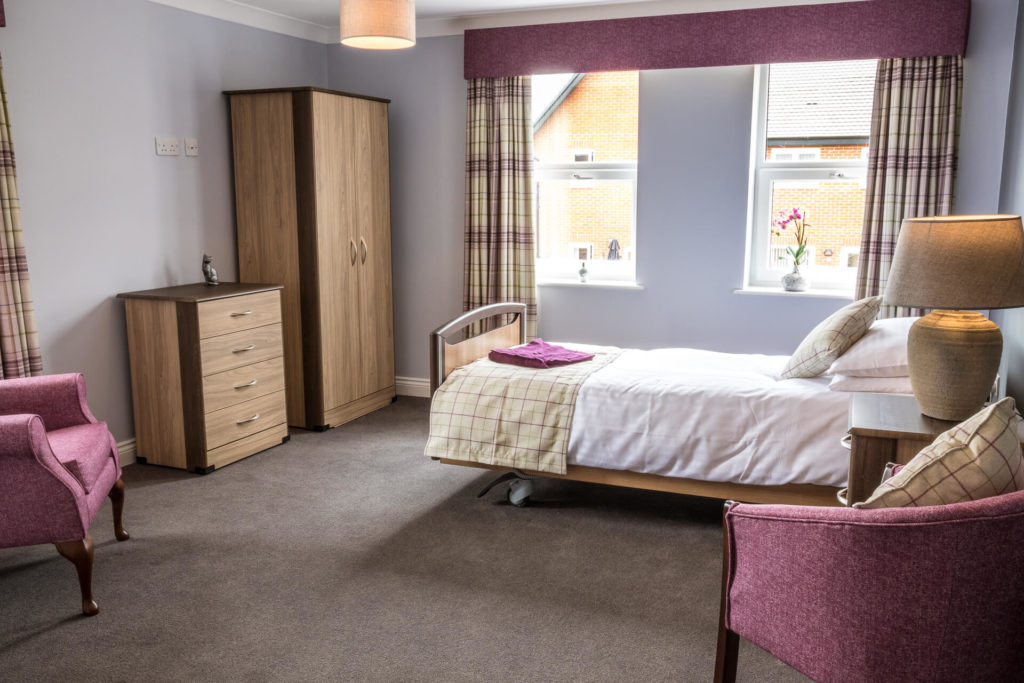 A colour image of the interior of a residential room at The Lawns Care Home, Kempsey, Worcestershire. Taken from the door looking inwards the image shows the single bed, a wardrobe, a chest of drawers, a bedside table with a lamp, and two sitting chairs. The colour scheme is pridominately a brown/grey colour with the beige tartan curtains, the chairs and the curtain pelmet are in a light burgundy colour.