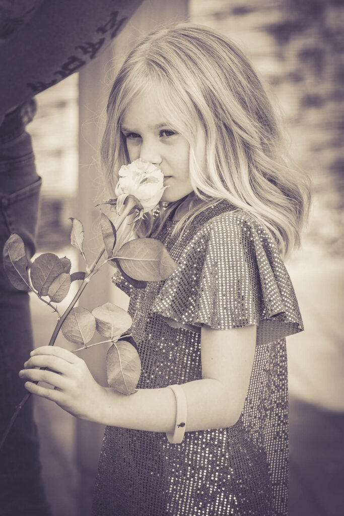 A little girl holding a rose in her hand puts it to her nose to smell it. 2020.