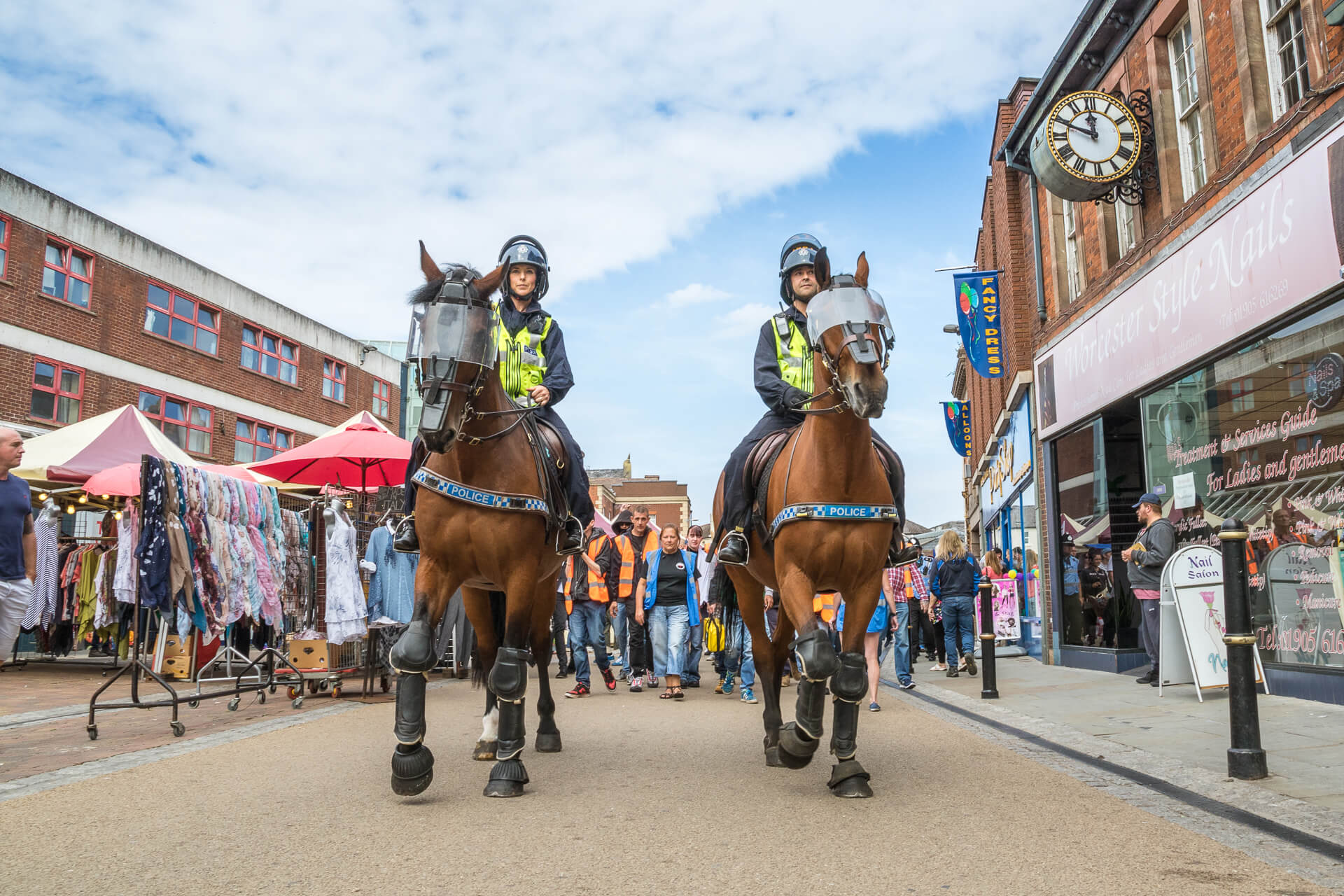 A wide angle low level shot of PC 3762 of the Avon & Somerset Police and her colleague as they ride their mounts at the BNP Marches in Worcester in 2019. They are seen here wearing protective riot gear, their helmets have the vizors up as lead off the protestors at the start of the march.