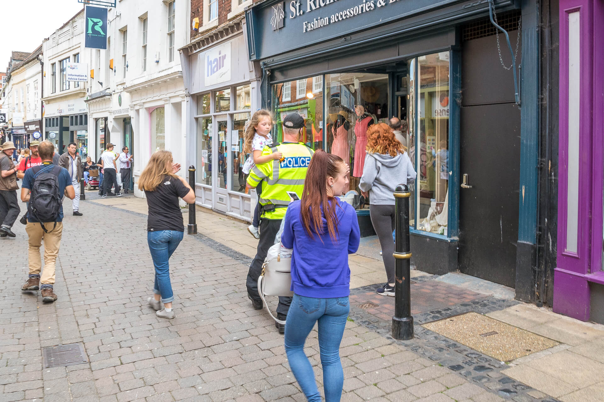 A colour image of a small girl who has been picked up by, and who is now being carried to safety by a Policeman at the BNP Marches in Worcester in 2019. She was in danger of being 'consumed' by the crowd and this act saved her from doing so.