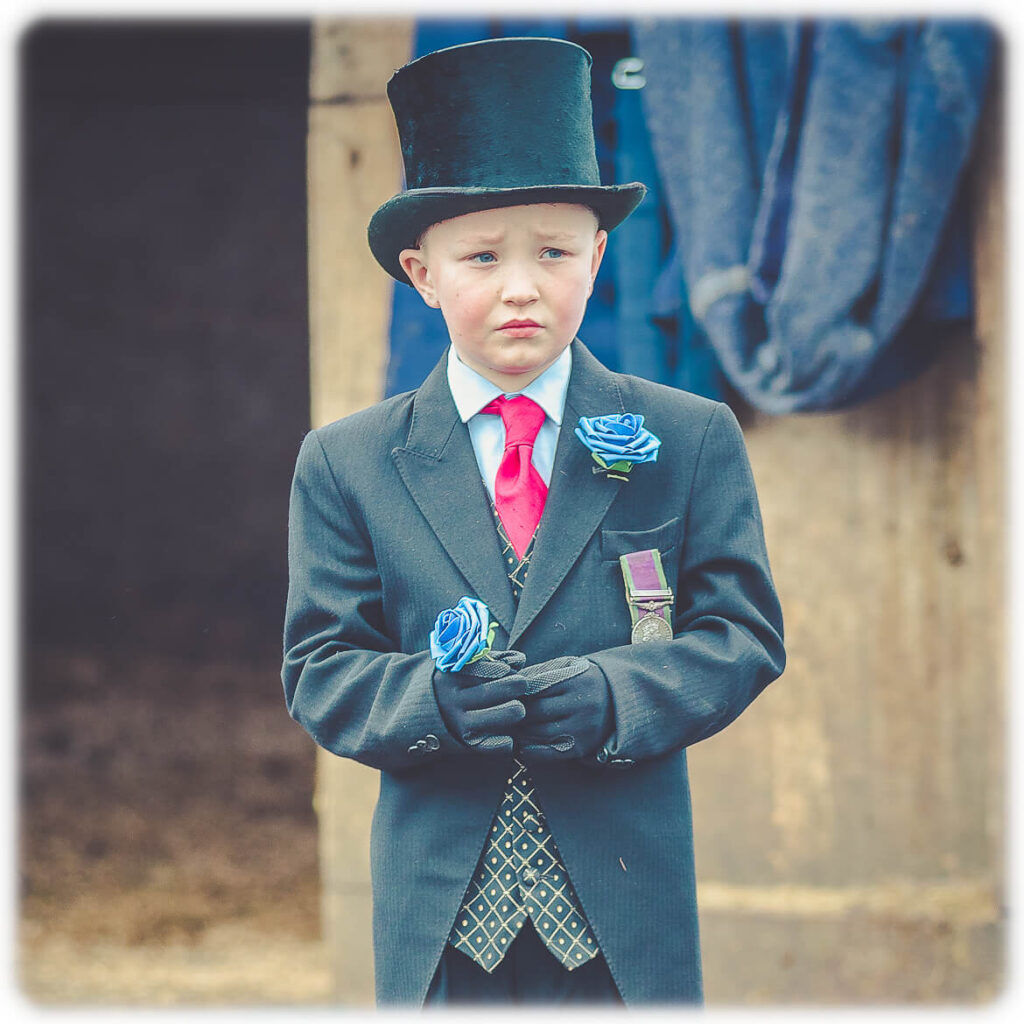 A young boy in a top hat and tails wearing his Grandfathers General Service Medal, whilst holding a blue rose, watches his Grandfathers funeral procession preparations.