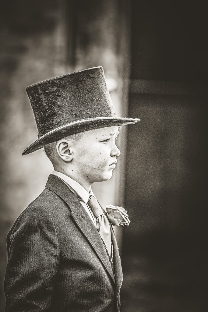 A young boy in a top hat and tails wearing a rose in his lapel watches his Grandfathers funeral procession.