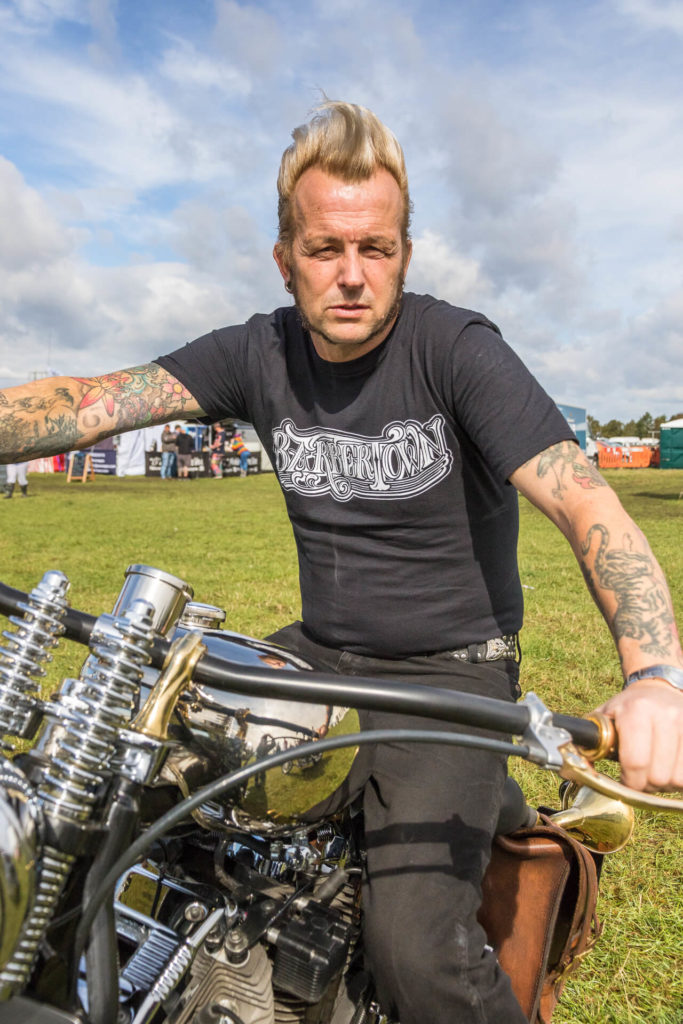 Gaz, frontman of The Delray Rockets, seen in colour and in a relatively close up shot as he sits astride a vintage motorbike at The Dubs of Anarchy Festival 2019. He adopts a very James Dean(esque) pose. He wears black jeans, a black T-Shirt, and has his blonde hair in a typical 1950's Rock 'n' Roll style quiff.
