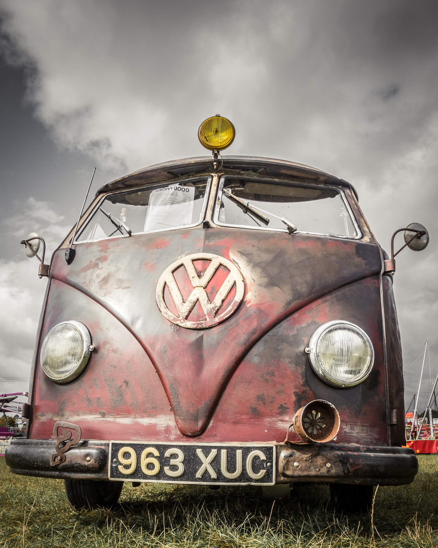 The front end view of a customised split screen VW T1 van in relative close up. This image, taken from low level, shows the dark red paint job of the van, and the predominantly large iconic VW white badge. This image was take at the Dubs of Anarchy show in 2019.