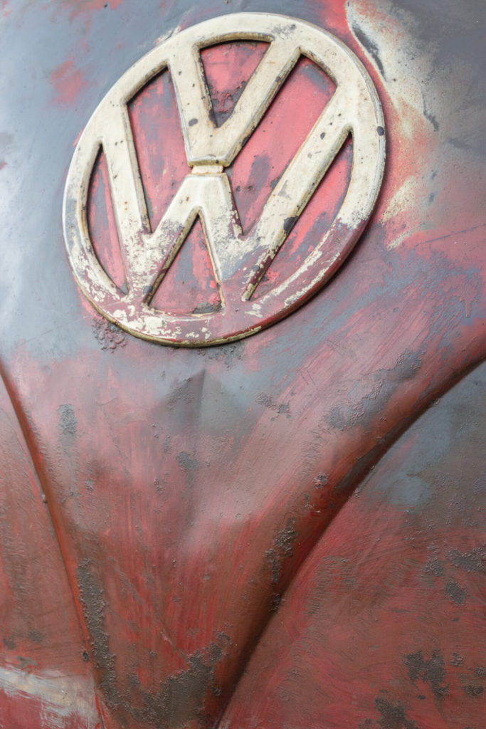 The badge of a customised split screen VW T1 van in close up. This image shows the dark red paint job of the van and the predominantly white badge. This image was take at the Dubs of Anarchy show in 2019.