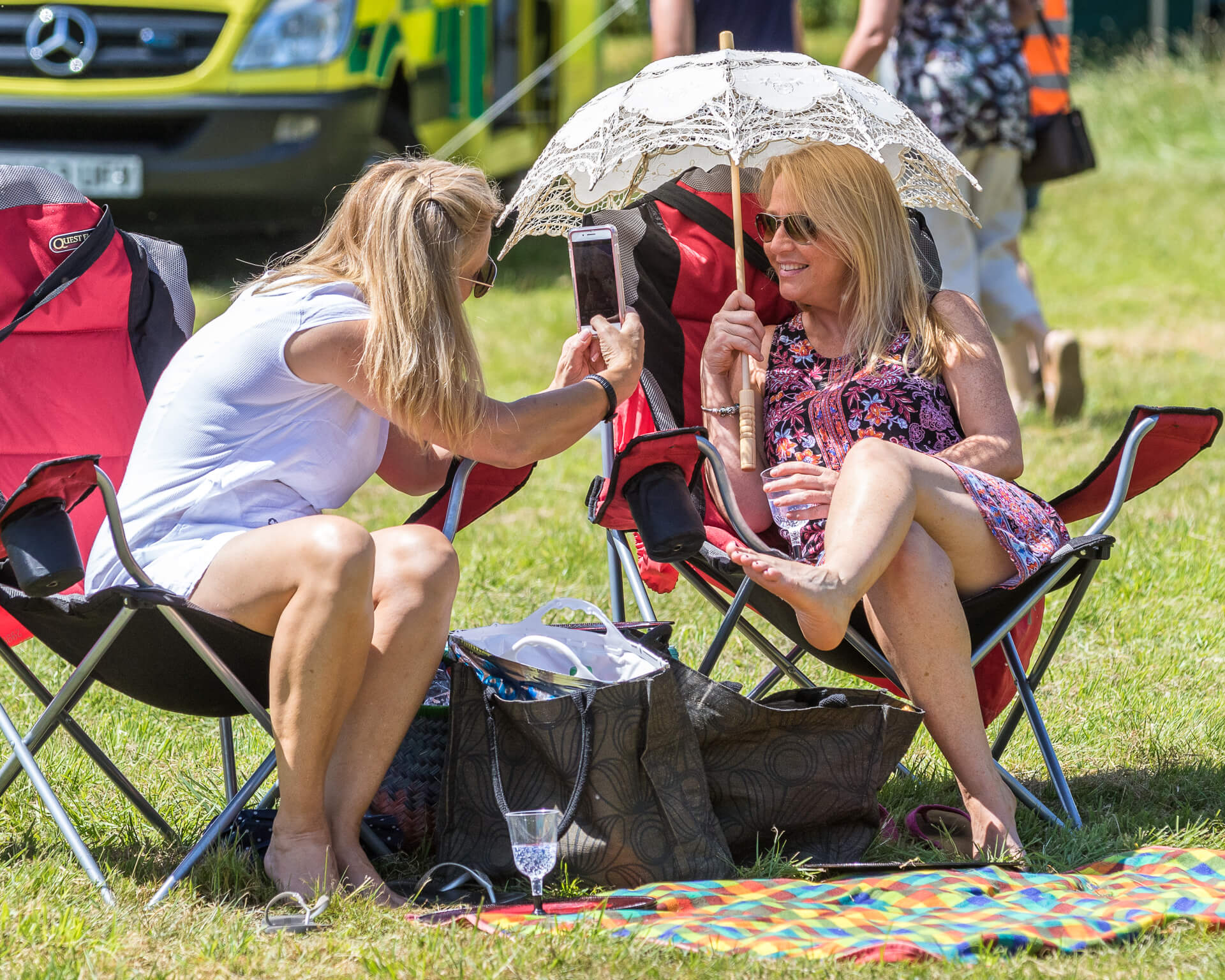 A colour image of two long blonde haired ladies at Mantonfest, Marlborough, Wilts, sat together on collapsable chairs in the sun, waiting for the start of the day. One, in a flowery dress and sunglasses, and holding a glass of something cold holds a parasol over herself with her right hand as her friend, dressed in a white top and white shorts, takes her photo with a mobile phone. Both are bare foot.