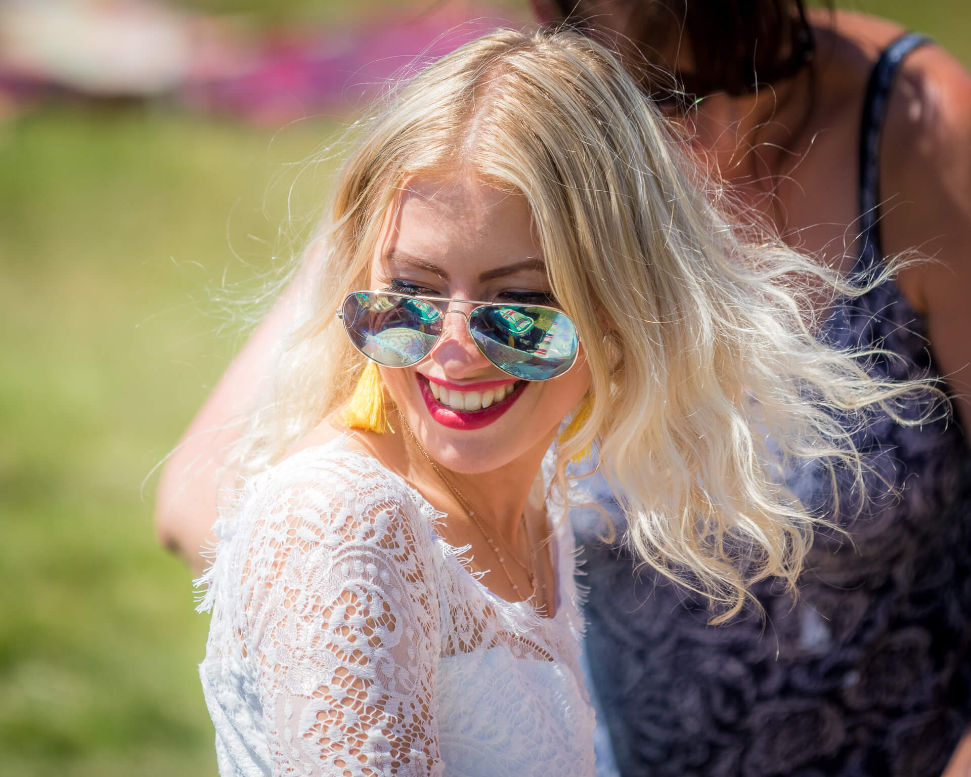 A female festival goer, seen in this chest up colour image, enjoying herself at Mantonfest in 2018. She is slim, she has shoulder length blonde hair, and wears a lightweight white summer top. She has wears a pair of 'aviator' style sunglasses, which are perched halfway down her nose, and bright red lipstick.