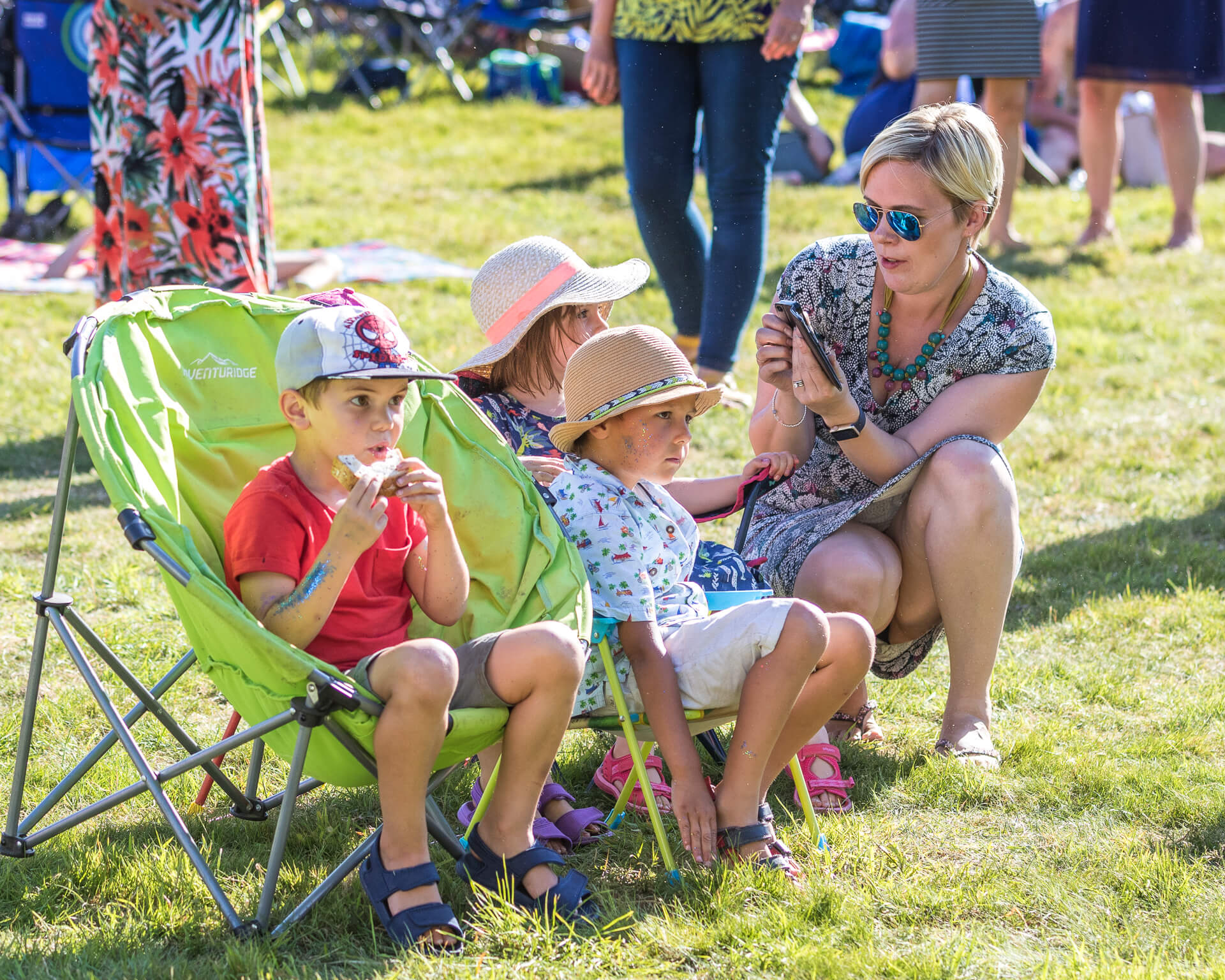 A family group of Mum and 3 children, seen here in colour, at Mantonfest in 2019. The 3 children, one of which is eating a sandwich, are engrossed in something in the stage area whilst Mum, who is squatting down to the side of them, tries to take a photo of them with her mobile phone. They appear to have zero interest in her efforts.