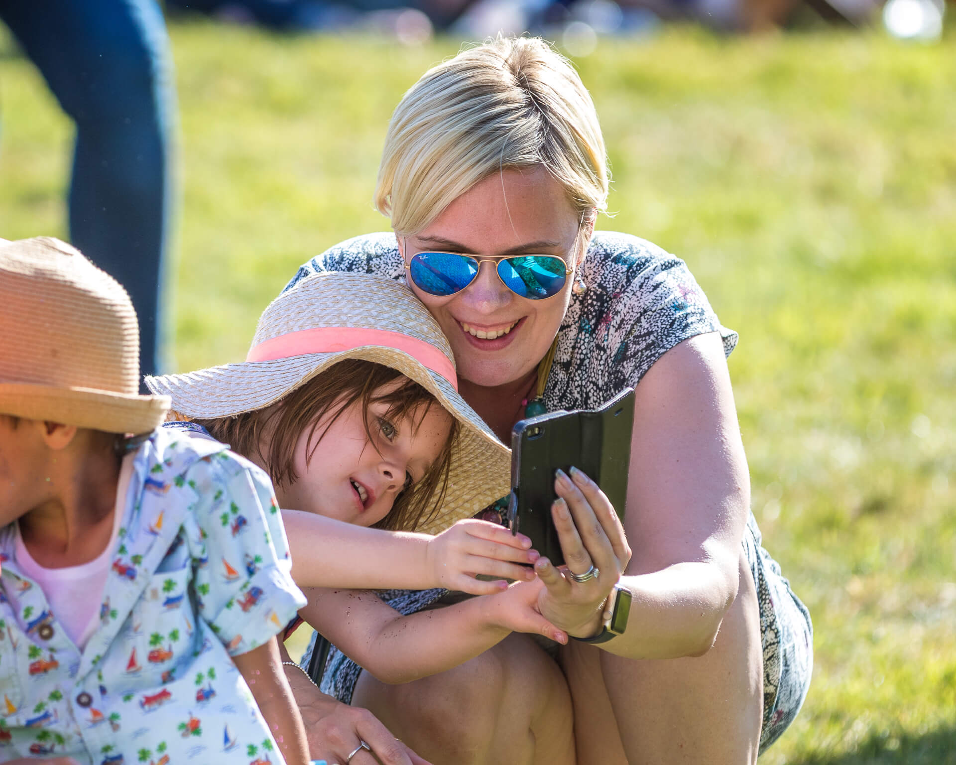 A close in shot of a short blonde haired Mother and 1 of her 3 children (who wears a floppy sun hat), seen here in colour at Mantonfest in 2019. The child is leaning over towards her Mother (who is in a squatting position next to her), as she try's to look at the screen of her Mothers mobile phone.