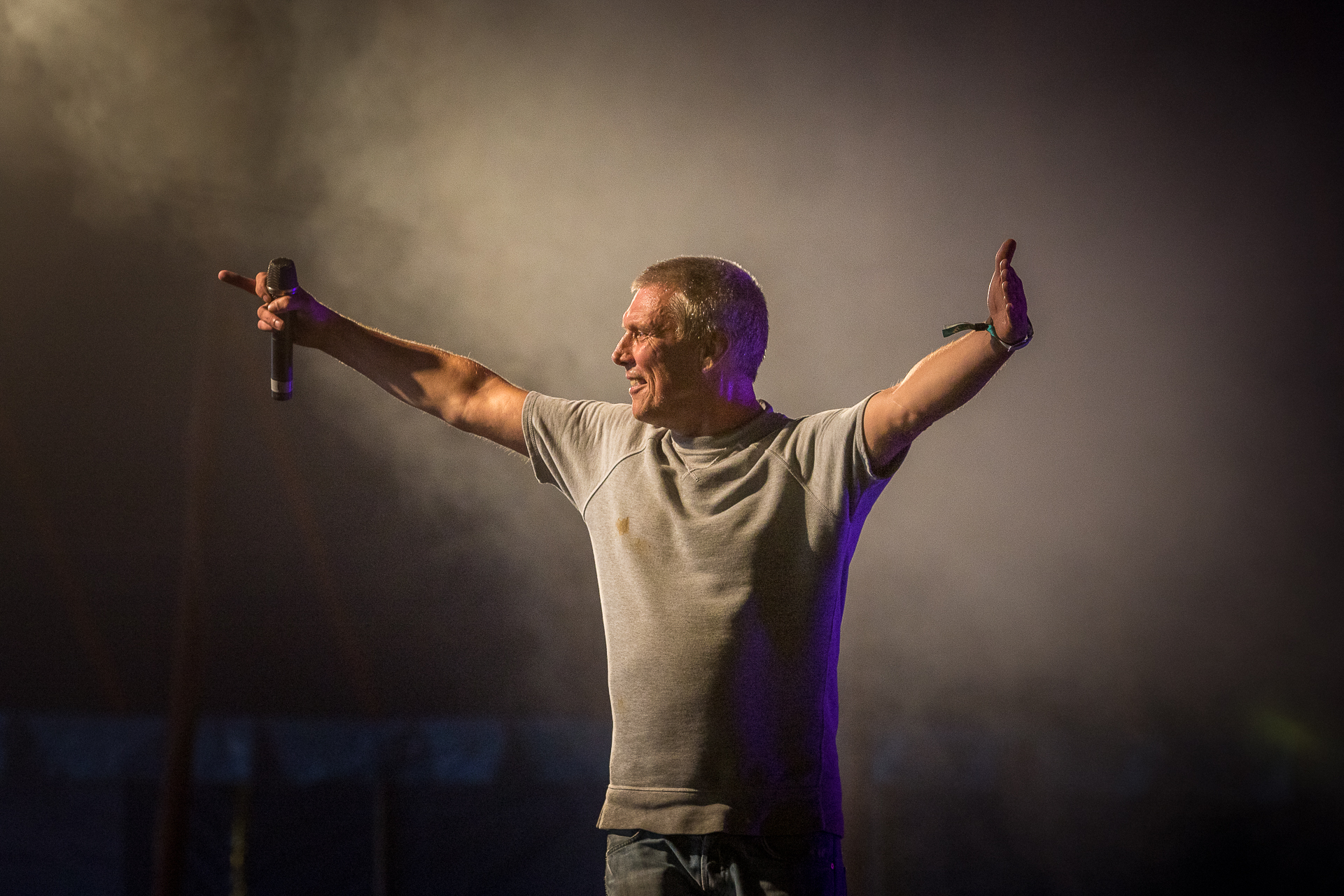 A smiling Bez on stage, arms outstretched, performing as a solo artist at Lakefest 2019.