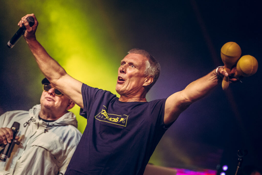 Bez (of the Happy Mondays) stands on stage, arms outstretched, at Lakefest 2019 holding Maracas in his left hand and a microphone in his right hand. Stood to his rear right is Shaun Ryder the group's lead singer.