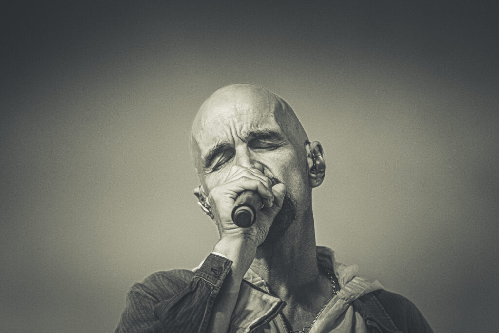 An emotional B&W head & shoulders shot of Tim Booth of James singing at Lakefest 2019