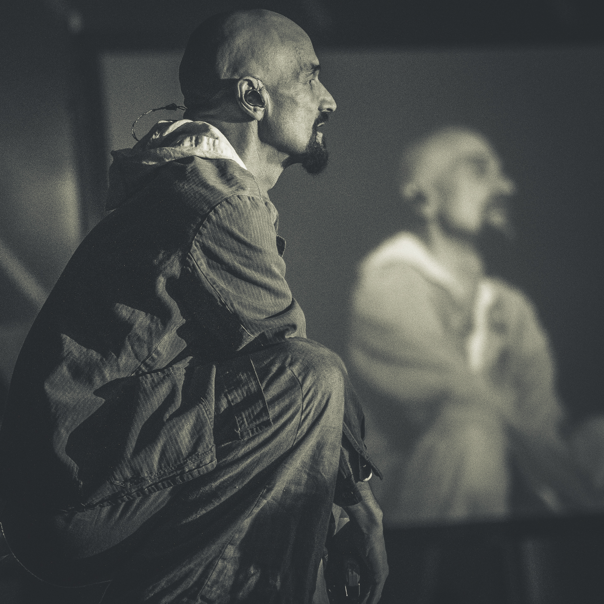 A B&W shot of Tim Booth of James squatting down whilst on stage at Lakefest 2019. A different out of focus shot of him on the on stage screen can be seen in the background.
