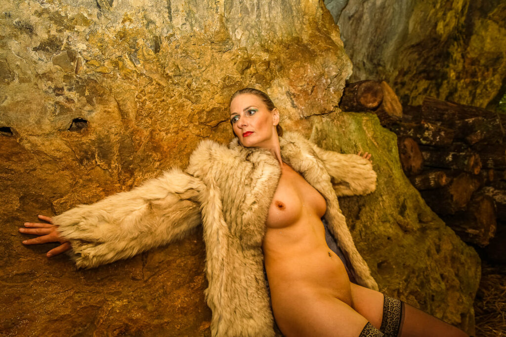A colour thigh upwards image of Liz as she leans, arms outstretched, against a cave wall. She wears nothing save a fake fur coat and stockings as she looks into the distance along her right arm.