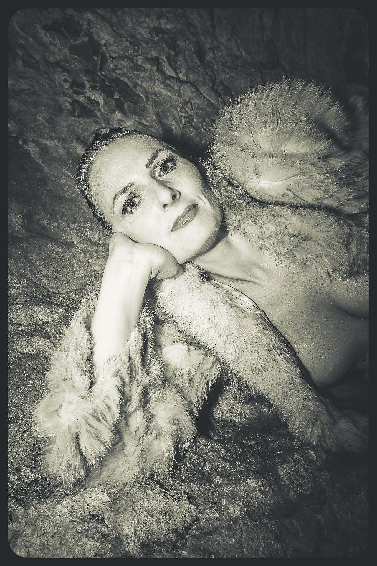 A Black & White 1960's style waist up image of Liz as she leans (with her right arm under her chin) against a cave wall. She wears nothing save a fake fur coat and as she looks into the camera.