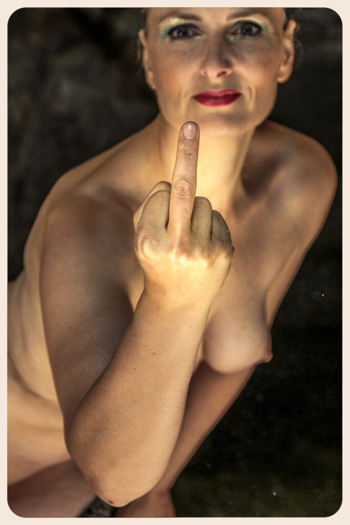 A colour waist up image of a naked Liz as she gives 'the finger' to the camera whilst looking directly into the lens. Her extended right hand and her middle finger are both in sharp focus, whilst her body is slightly out of focus, thus emphasising her gesture!