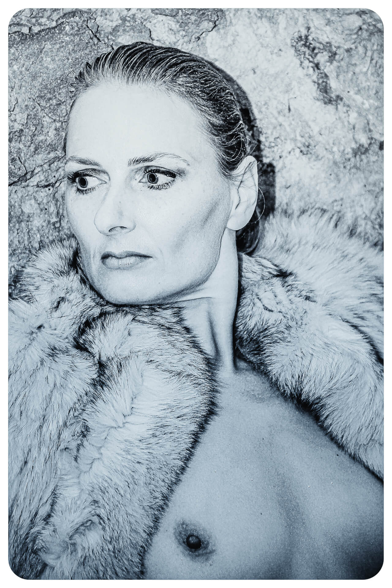 A harsh silvery Black & White 1960's style chest up image of Liz as she leans against a cave wall. She wears nothing save a fake fur coat pulled tight around her neck (but open at the chest allowing her breasts to show) as she looks away from the camera.