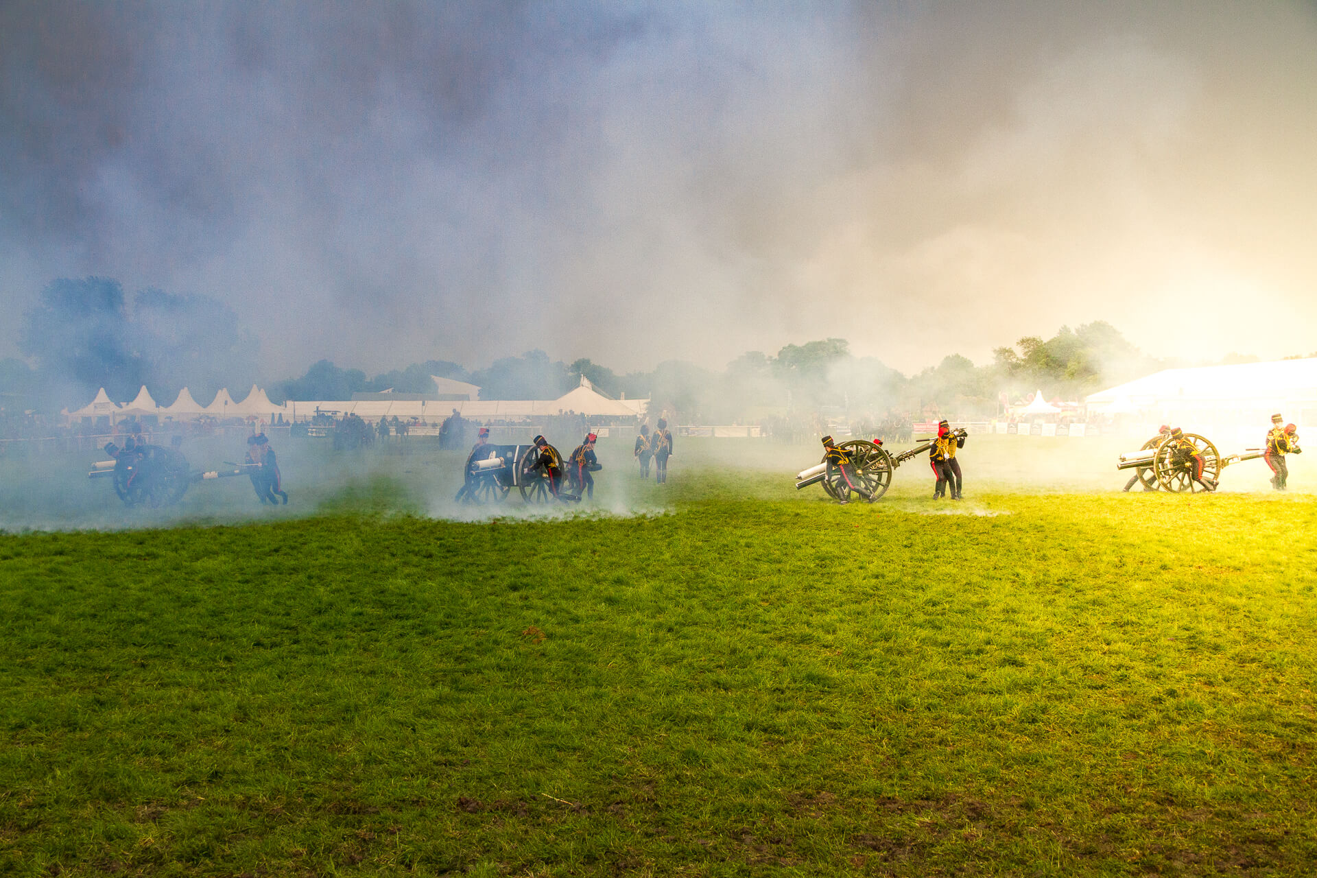 A wide angle image of the arena at the 3 Counties Show Ground, Malvern. Displaying in the arena are the men and the guns of the Kings Troop Royal Horse Artillery, they are seen manoeuvring their guns by hand as part of their display. At points in the display blank rounds are fired from the guns, smoke from an earlier firing can be seen blowing across the arena.