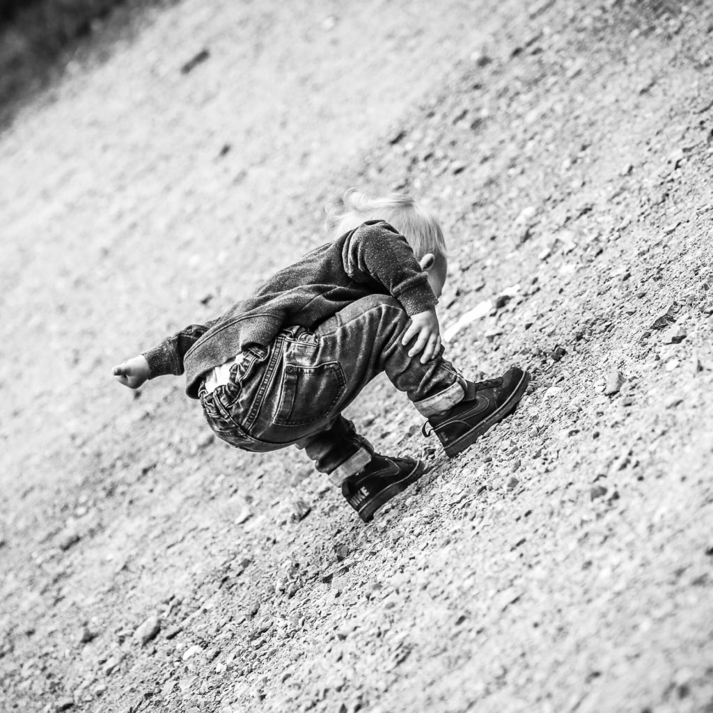 A black & white image (taken at a 45 degree angle) of a lone toddler as he bends and leans forward to look at something on the ground in front of him, with an ability only toddlers have. His left arm sticks out to his left hand side as balance whilst his right holds his right calf as stability.
