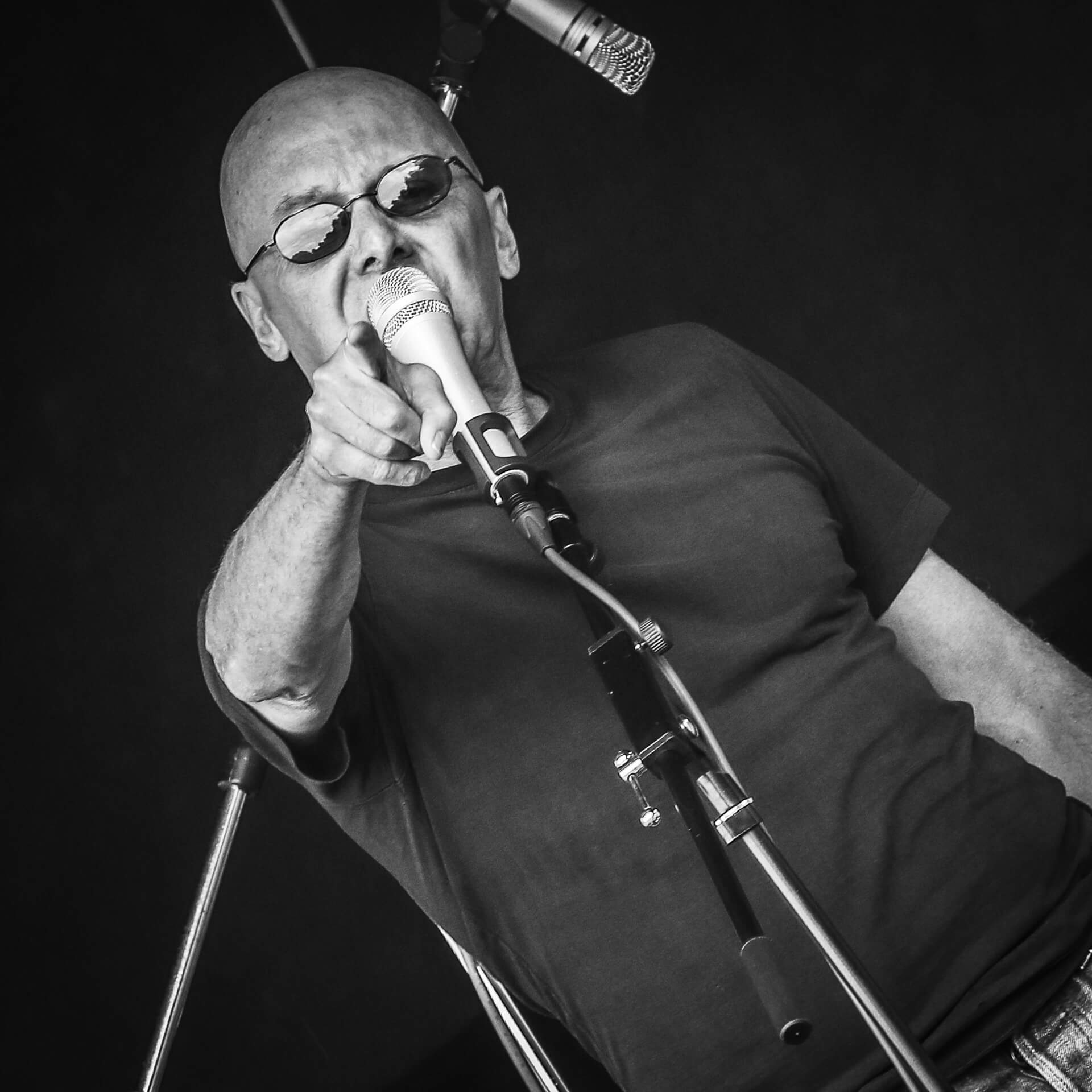 The frontman of a band playing on the acoustic stage at Mappfest, Malvern is seen pointing at the camera in this black and white image whilst on stage. The image, taken at a 45 degree angle, shows him from the waist up, he wears sunglasses and has a bald head.