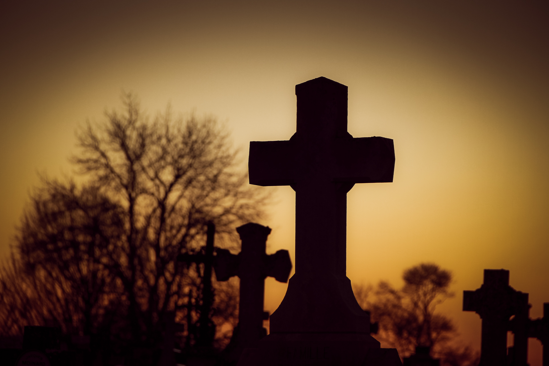 A tobacco coloured image of a silhouetted stone cross grave marker in the cemetery in Rom, France. The cross is set against a beautiful sunset near in France.