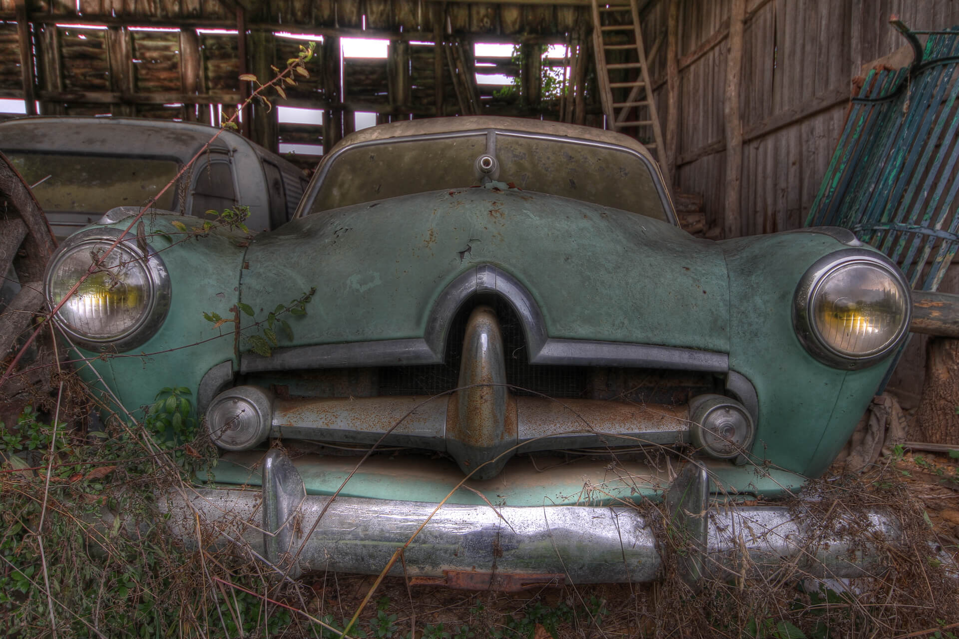 A (HDR) High Dynamic Range image of an abandoned green coloured vintage car left in an open wooden lean to in Couhe in France. The image was taken looking at the vehicle from bumper height. Behind it sits what appears to be an abandoned grey Citroen Van.